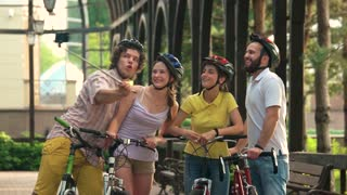Young funny friends with selfie stick. Cheerful group of young cyclists posing and gesturing thumbs up using monopod in park. Young people spending good time together.