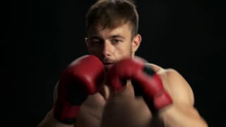 Young handsome guy practicing a punch. Young muscular man with naked torso boxing in red gloves, black background.