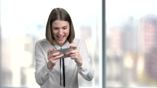 Young joyful woman playing on smartphone. Funny business woman playing online game on phone, blurred background. Female corporate having a break.