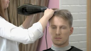 Young man getting hair dryed. Female barber working, blow dryer.