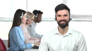 Young man with beard in office, bright room. Hypocritical sacrastic young man in office, huge windows background.