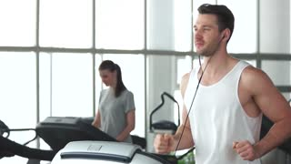 Young muscular man running on treadmill. Handsome guy running on track at modern gym.