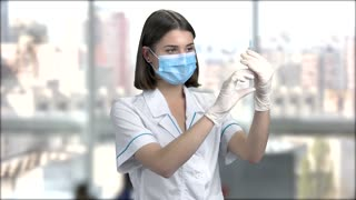 Young nurse with medical syringe. Young female doctor or nurse in surgical mask holding an injection in her hand on blurred background.