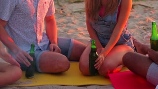 Young people clinking bottles. Company sits on the beach. Welcome to our humble party. Invite friends for a beer.