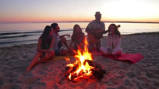 Young people dance and sing on the beach. Camping on the island. Youth with a guitar singing songs. Friendly company meets the dawn. Youth recreation in nature.