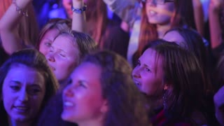 Young people dancing at a concert with hands up.