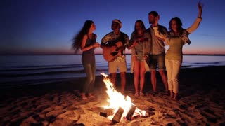 Young people having fun around the campfire. Young guys and girls play guitar and sing. Tourist group in the campaign.