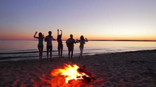 Young people meet dawn near campfire. Young people at the picnic. Funny friends relaxing on the island. Guys and girls dance around the fire. Camping trip.