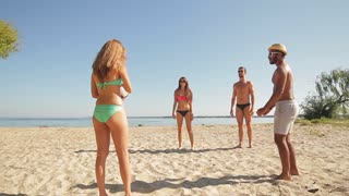 Young people play volleyball. Daytime at the beach. Active leisure in summer. Company of friends on vacation.