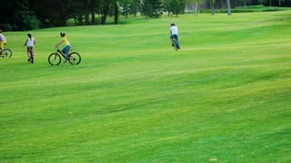 Young people riding bicycles outdoors. Group of young friends cycling on nature background. Bikers on golf field. Happy summer trip. Sporty company on bicycles.