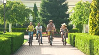Young people riding bicycles, slow motion. Four smiling young cyclists on bicycles in park. Happy time spending with best friends.
