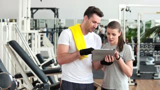 Young people using digital tablet at gym. Young sporty attractive people looking at computer table and talking at fitness club. Sport and technology.