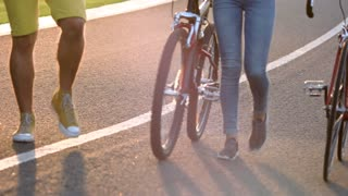 Young people walking with bicycles. Legs of young people with bikes, summer day. Active lifestyle concept.