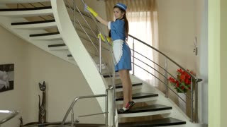 Young pretty housemaid working. Attractive woman with bent leg.