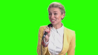Young pretty woman talking with microphone. Young smiling business lady holding microphone and speaking to audience on chroma key background.
