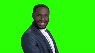 Young sexy stylish businessman on green screen. Smiling self-assertive dark-skinned businessman on Alpha Channel background.