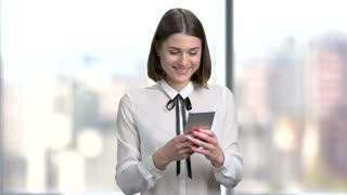 Young smiling woman using smartphone. Happy cherful female corporate typing a massage using touch screen phone, blurred background. People, business, technology.