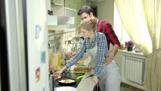 Young woman and man cooking. Romantic couple in the kitchen.