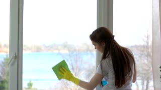 Young woman cleaning window. Girl in rubber gloves working. Glass detergent advertising.