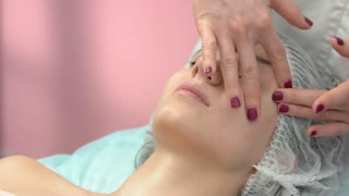 Young woman getting face massaged. Masseuse working with caucasian girl. Facial massage guide for beginners.