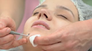 Young woman having face cleaned. Cosmetician using blackhead remover.