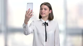 Young woman holding smartphone and talking. Beautiful young lady in formal blouse talking via internet, blurred background.