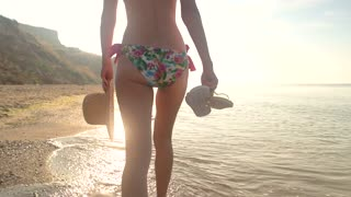 Young woman in bikini walking. Lady carrying a beach hat. Towards the sun.