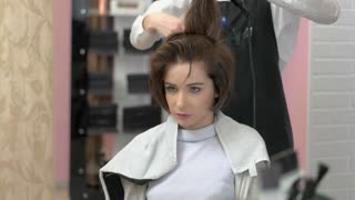 Young woman in hairdressing salon. Hairdresser using blow dryer. Ultimate hair styling guide.