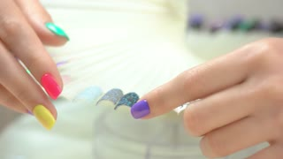 Young woman manicured hands. Nail art samples and female hands with multicolored summer manicure. Girl in nail salon.