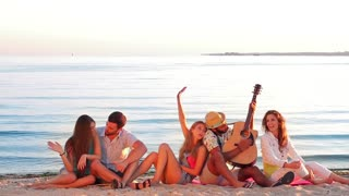 Youth emotionally sings and plays guitar. Music group resting on the sea. Party on the island. Tourist journey. Friendly company meets sunrise on the seafront.