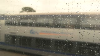 View from wet train window. Blurred road and nature. Leave home town forever.