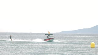 Water skier in motion. Motorboat on mountain background. Make your vacation unforgettable.