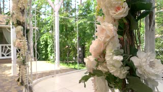 Wedding arch with flowers. Light-colored roses and leaves. Holiday of unity and love.
