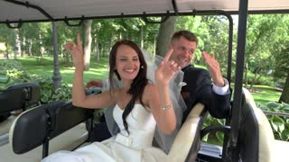 Wedding couple in a vehicle. People sitting and dancing. Ride into new life. Married and happy.
