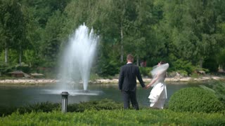 Wedding couple near fountain. Bride and groom outdoors. Newlyweds admire the view. Fate brought us together.