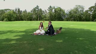 Wedding couple on picnic. Bride and groom on meadow. Can you juggle. Impress the fiancee.