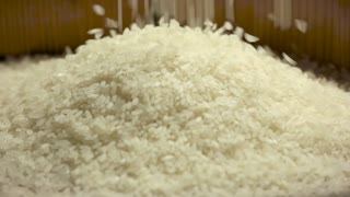 White rice falling in slow-mo. Raw groats closeup.