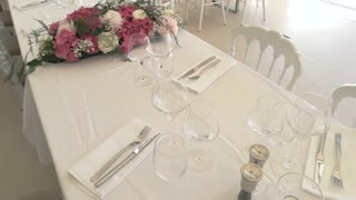 Wineglasses and cutlery on table. Pink and white flowers. Have lunch in best restaurant.