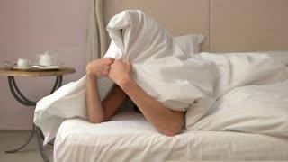 Woman hiding under blanket. Smiling lady in bedroom. Let's play hide and seek. Girl in good mood.