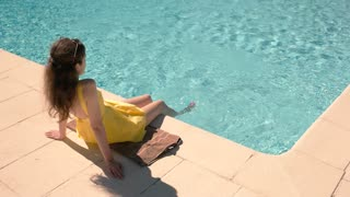 Woman sitting near swimming pool. Blue water and sunlight. Rest and recover.