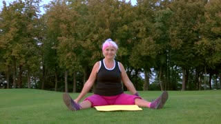 Woman stretching and smiling. Lady sitting on a mat. Breathe in and breathe out. Exercises in fresh air.