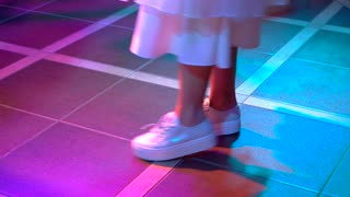 Woman's feet dancing on floor. Lady in dress and sneakers. It's time to dance. The stylish dancer.
