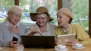Women at cafe table laughing. Cheerful ladies with gadgets. Most hilarious photos.
