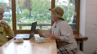 Women with laptop and tablet. Old ladies in cafe talking. Online shopping benefits.