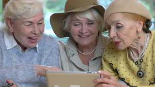 Women with tablet laughing. Cheerful senior ladies.