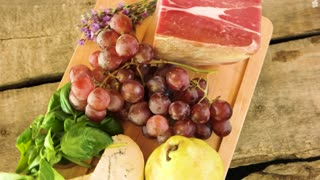 Wooden board and raw food. Frozen meat, cheese and fruits. Tips for healthy diet.