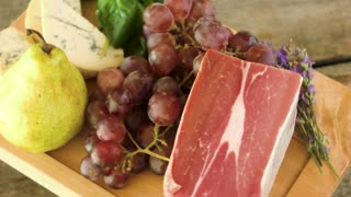 Wooden board with raw food. Frozen meat, cheese and grapes. Best dieting tips.