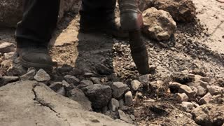Worker holding pneumatic hammer drill. Dirt and small rocks. Roads need repair. Break and build.