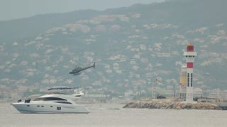 Yacht near lighthouse. Helicopter in motion. Coast guard at work.