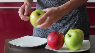 Young housewife peels apple for fresh juice. Delicious apples lay on a plate.
